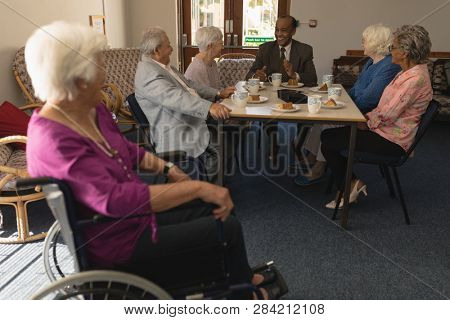Disable senior woman with happy group of senior friends having fun at nursing home