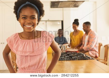 Front view of happy African American girl looking at camera in a comfortable home with family in the background