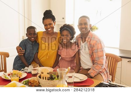 Front view of happy African American family looking at camera in dining room in their comfortable home