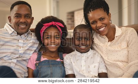 Portrait of happy African American family sitting on the sofa and looking at camera in a comfortable home