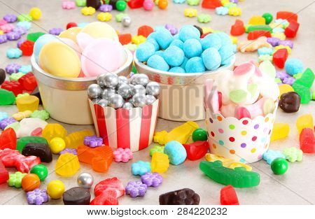 Assorted variety of sweet sugar candies includes bonbons, gummy bears, gum balls and sugar fruit slices. Candy background for a kids birthday party.