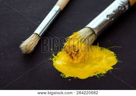 Artist brushes on black background with yellow paint close up