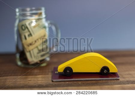 Saving money for vacation theme with yellow wooden car and money in jar