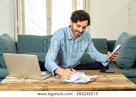 Happy Attractive Latin Man Calculating Home Finances