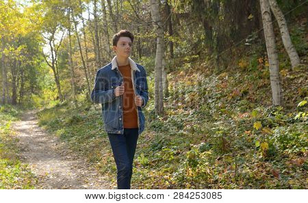 Teenager In The Autumn Path In Forest