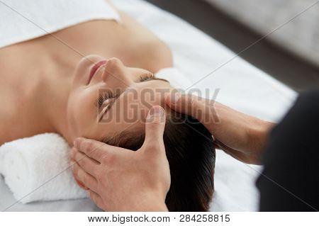 Young Beautiful Woman Enjoying A Back Massage. Professional Massage Therapist Is Treating A Female P