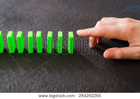 Hand Ready To Push Domino Piece To Cause Chain Reaction.