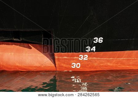 Detail Of A Red And Black Ship Prow With A Waterline (water Level Measurement) And Anchor