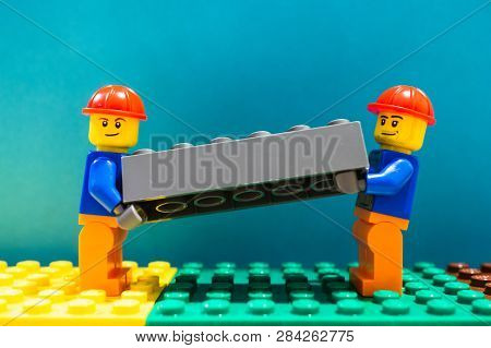 Poznan, Poland - February 13, 2019: Two Lego Construction Workers With Helmet Lifting Together As A