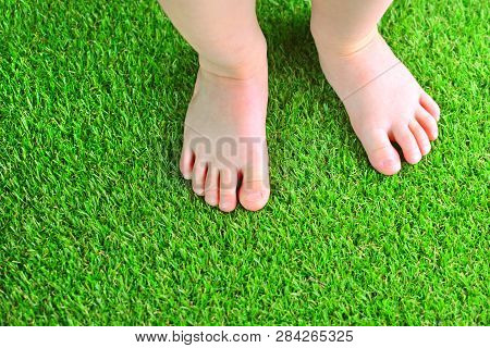 Artificial Turf Background. Tender Foots Of A Baby On A Green Artificial Grass Floor.