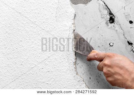 Old woodchip wallpaper is removed or scraped off the wall with a spatula or painter's spatula poster
