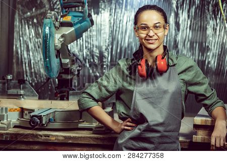 Smiling craftswoman grinding timbers with special machine. Beautiful woman wearing safety glasses. Concept of joiners shop and woodworking. Gender equality. Male profession poster