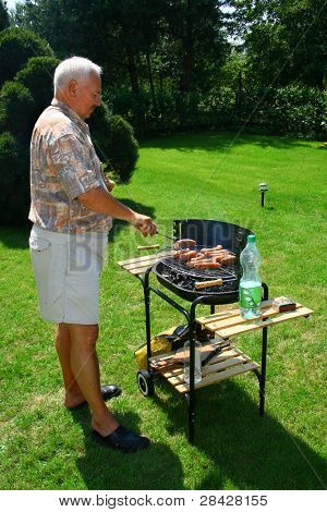 Old man outside cooking/ barbecuing