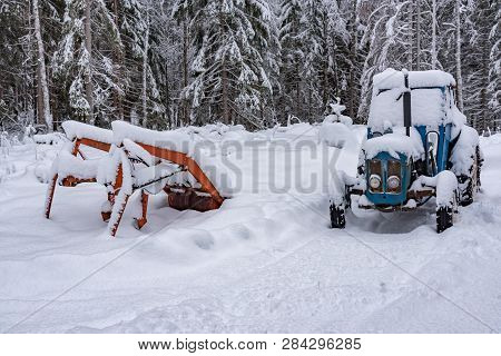 Old Blue Tractor Standing Covered In Snow