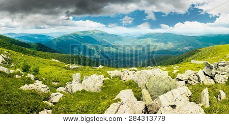 Panorama Of Mountain Landscape In Summer. Rocks Lay Among On A Grassy Slope Down To The Valley. Beau