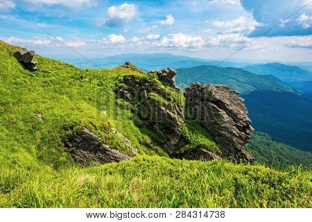 Rocky Cliff On A Grassy Slope. Beautiful Scenery In Mountains. Huge Ridge In The Distance. Wonderful