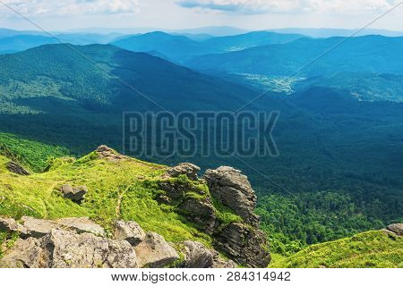 Rocky Cliff On A Grassy Slope Above The Valley. Beautiful Summer Landscape In Mountains. Huge Ridge