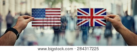 Two Hands Holding Different Flags, Uk Vs Usa On Politics Arena Over Crowded Street Background. Futur