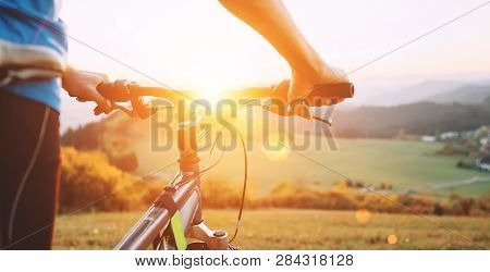 Man With Bike Stay On The Top Of Hill And Enjoying The Sunset. Man Hands On The Bike Steering Wheel