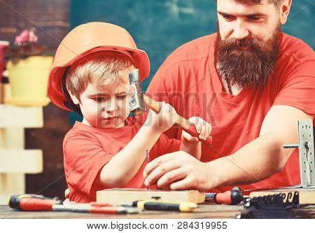 Little Assistant Concept. Boy, Child Busy In Protective Helmet Learning To Use Hammer With Dad. Fath
