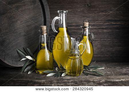 Bottles Of Extra Virgin Healthy Olive Oil With Barrel Background
