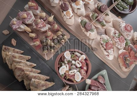Top View Of Spanish Tapas Snacks With Olives, Anchovies And Peppers. Vintage Style