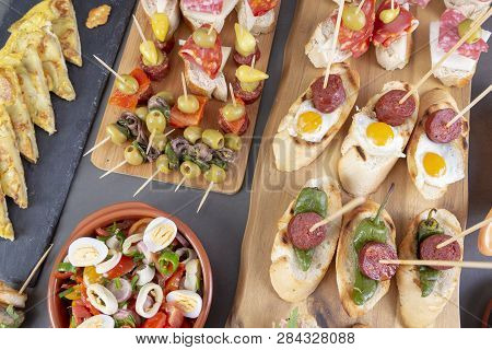 Top View Of Spanish Tapas Snacks With Olives, Anchovies, Tortilla, Patas And Peppers