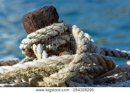 Old Rusty Iron Mooring Bollard With White Ropes