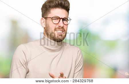 Young handsome business man wearing glasses disgusted expression, displeased and fearful doing disgust face because aversion reaction. With hands raised. Annoying concept.