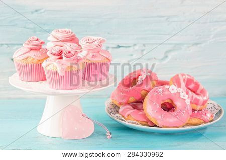 Pink donuts and cup cakes on a blue background