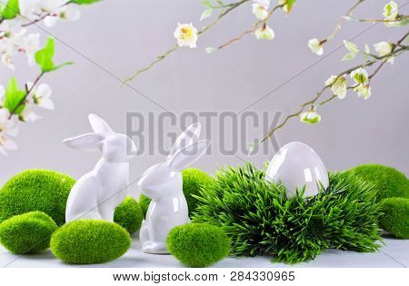 Ceramic easter rabbits and egg on a grey background