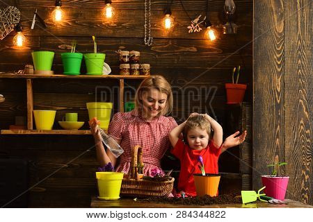 Kid Concept. Happy Kid Potting Plants With Mother. Kid Learn Planting Flower In Pot With Soil. Littl