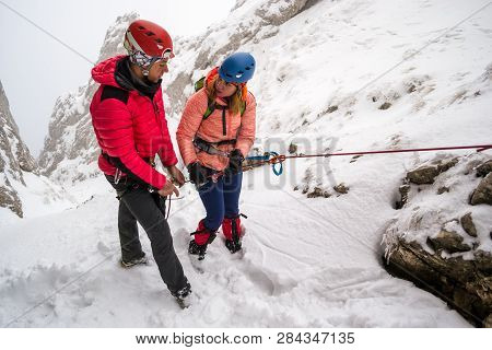 Two Mountaineers Discussing Safety Abseiling Procedures Before Rappeling Down A Snowy Chutte, On A D