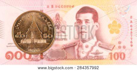 50 Thai Satang Coin Against 100 New Thai Baht Banknote