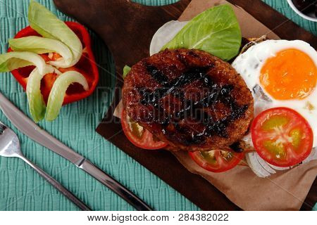 junk food big beef hamburger fried eggs on dark wood plate with modern cutlery ketchup sauce and pickels on blue mat isolated over white background