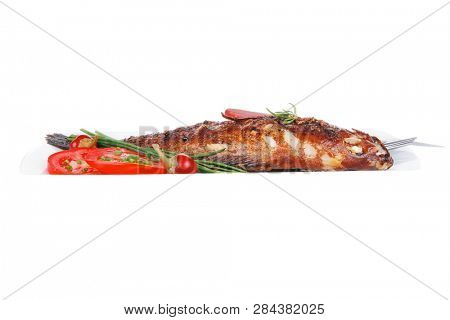 savory isolated on white: whole fryed sunfish over plate with tomatoes lemons and peppers