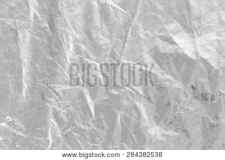 metalic Silver foil background with shiny crumpled uneven surface for texture and background poster