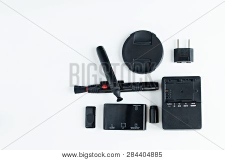 Top View Of Photographer Concept With  Battery Charger Camera, Memory Card  , Lens Cap, Cleaning Pin