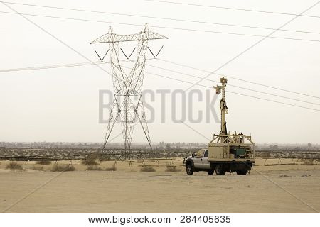 Border Patrol Surveillance Vehicel With Mexico And Barrier Wall In The Background
