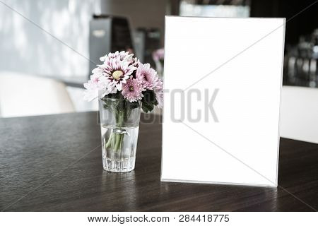 Mock Up White Label For Blank Menu Frame In Restaurant Cafe With Plant Flower. Stand Booklet Sheets