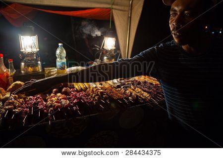 Zanzibar, Tanzania - May 01, 2018: Zanzibari Street Vendor And Chef Show His Snacks At Night Street