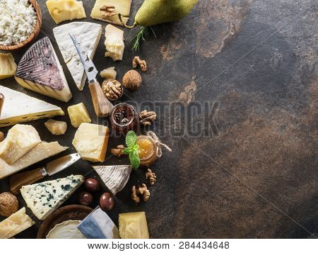 Cheese platter with organic cheeses, fruits, olives and jam on stone background. Tasty cheese starter.
