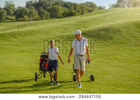 Boy And Man Golfers Walking On Golf Course With Carts