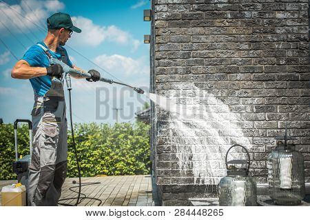 Brick House Wall Pressure Washing With Special Cleaning Detergent. Caucasian Men In His 30s. Taking