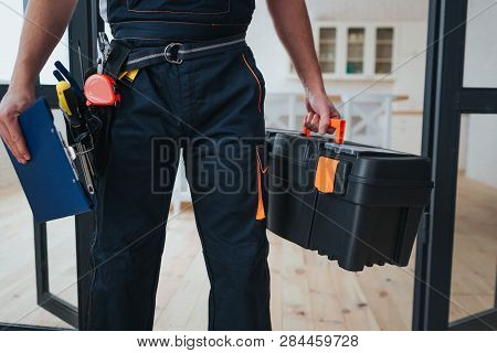 Cut View Of Handyman Holding Tool Box And Plastic Tablet In Hands. He Stand In Kitchen. Guy Wear Spe