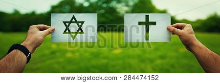 Religion Conflicts As Global Issue Concept. Two Hands Holding Different Faith Symbols, Judaism Vs Ch
