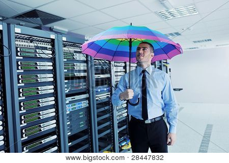 young handsome business man  engineer in .businessman hold  rainbow colored umbrella in server datacenter room  and representing security and antivirus sofware protection concept poster