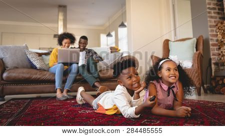 Side view of happy African American sibling lying on floor and watching television while parents using laptop on sofa in a comfortable home