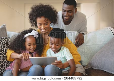 Front view of African American mother with her children using digital tablet on sofa while father looking them in a comfortable home