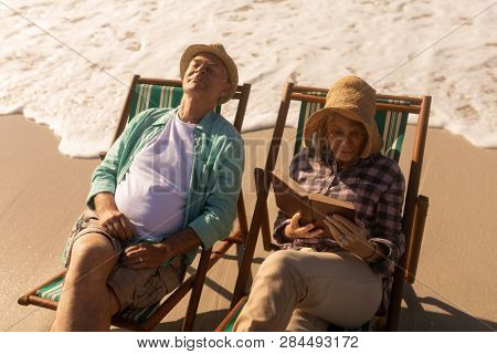 Front view of active senior woman reading a book while senior man relaxing on sun lounger at beach